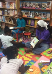 Dempstu Simmons Jr (Uncle DJ) reading to children in Days Bookstore, Bridgetown, Barbados as part of ArtsEtc's Read2Me! programme.